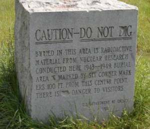 Mixed messages: A simple stone marker in Red Gate Woods, just outside Chicago, tries to both warn and reassure visitors to this public park. (Photo: Kevin Kamps, Beyond Nuclear. Used by permission.)
